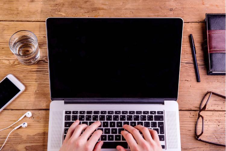 Schreibtisch mit Laptop, Handy, Brille, Notzibuch